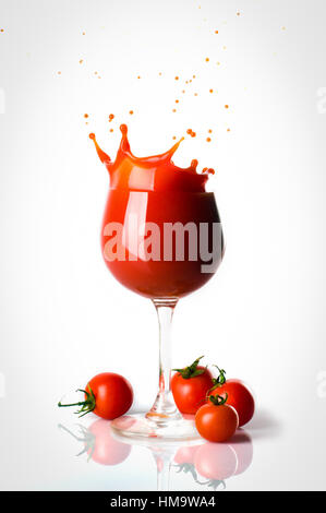 Splash o tomato juice in the glass and four small tomatoes seperated. - Stock Photo