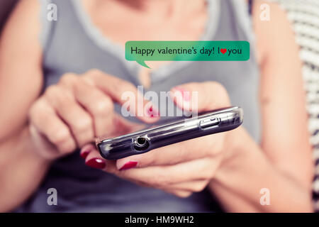 closeup of a young caucasian woman sending or reading a text message with a smartphone with the text Happy valentines - Stock Photo