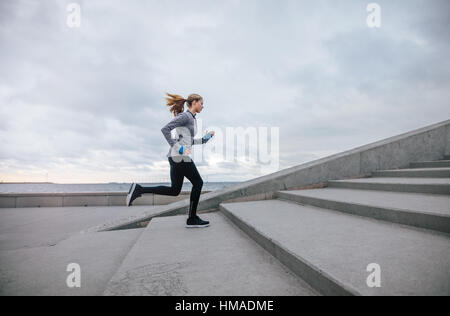 Side view shot of fitness woman running up on steps. Female runner athlete going up stairs. - Stock Photo