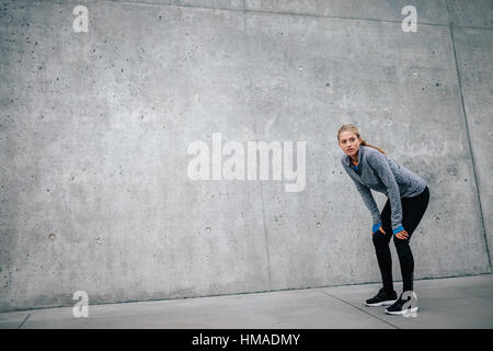 Full length shot of young beautiful female leaning on gray background while resting after everyday training. Woman - Stock Photo