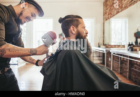 Handsome bearded man in a salon cape in the barbershop, with hairdresser adjusting the headrest of the chair. - Stock Photo