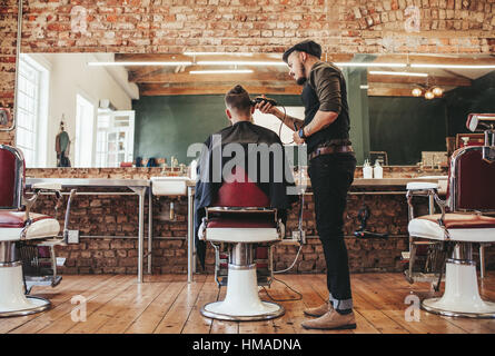 Rear view shot of handsome hairdresser cutting hair of male client. Hairstylist serving client at barber shop. - Stock Photo
