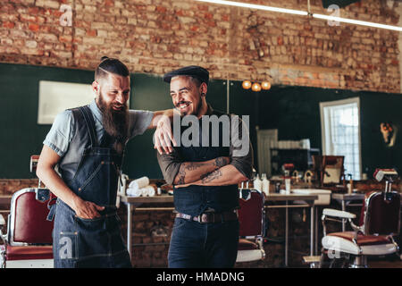 Shot of hairdresser with a man standing at barbershop. Hairstylist and client at salon - Stock Photo