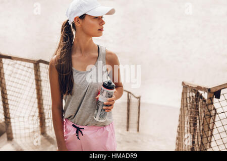 Shot of beautiful young woman at the beach taking a break. Fitness female with water bottle taking a break after - Stock Photo