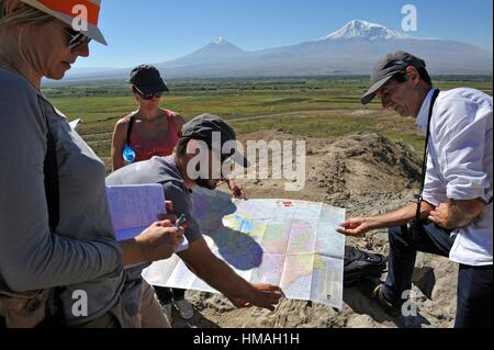 guide explaining geography with a map to a tourist group, in front of the Turkish border and Mount Ararat at Khor - Stock Photo