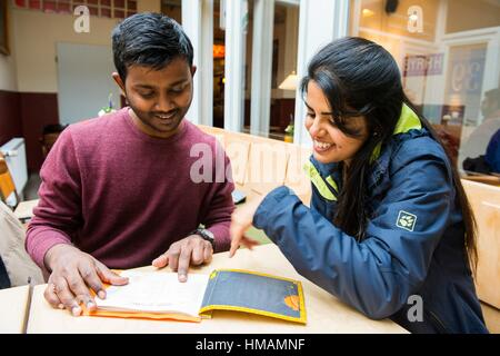 Aachen, Germany. Young Indian couple ordering a cup of tea, while visiting a down town cafe. - Stock Photo
