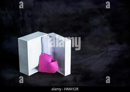 Valentine's heart in a open gift box. Origami Heart done with pink polka dot paper over abstract background. - Stock Photo