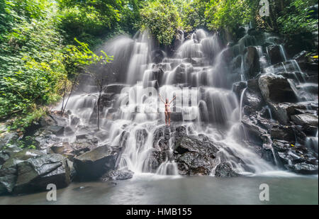 Woman standing on rock with outstretched arms, waterfall, Air Terjun Kanto Lampo, near Ubud, Bali, Indonesia - Stock Photo