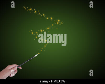 Magician with magic wand and stars on green. With copyspace, for magical results. - Stock Photo