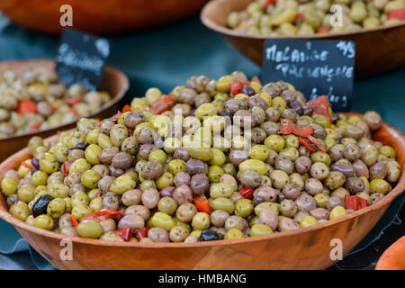 Close up image of wooden bowls with lots of mixed green, black and kalamata olives on a market stall in Charente - Stock Photo