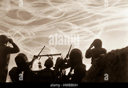 Alerted GIs of M-51 Anti-aircraft Battery are silhouetted against German sky streaked with vapor trails from allied - Stock Photo
