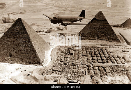 An Air Transport Command plane flies over the pyramids in Egypt.  Loaded with urgent war supplies and materials, - Stock Photo