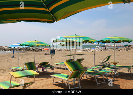 many parasols and deck chairs on the beach resort in summer - Stock Photo