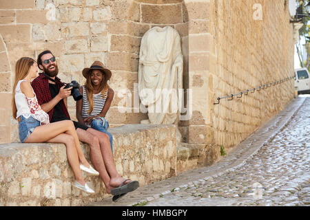 Friends sit looking at photos on a camera laughing, Ibiza - Stock Photo