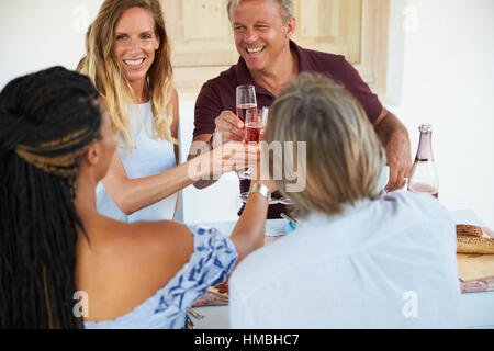 Two couples making a toast before dinner, close up - Stock Photo