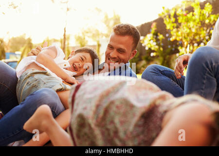 Parents Playing Game With Children On Blanket In Garden - Stock Photo