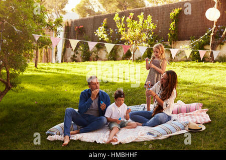 Parents Blowing Bubbles With Children On Blanket In Garden - Stock Photo