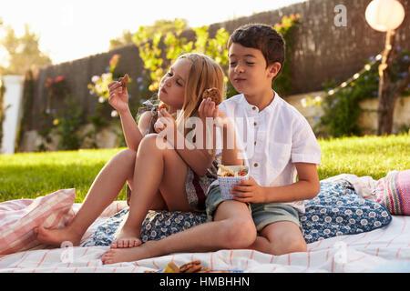 Two Children Enjoying Picnic On Blanket In Garden - Stock Photo