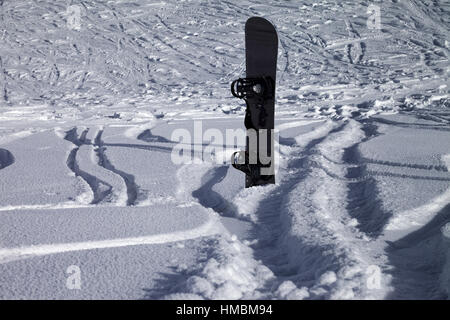 Snowboard in snowdrift and off-piste slope with new-fallen snow - Stock Photo