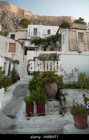 White painted narrow street and small houses in the traditional Anafiotika neighborhood of Plaka, Athens Greece - Stock Photo