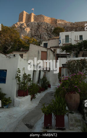 White painted narrow street and small houses in the traditional Anafiotika neighborhood of Plaka, Athens Greece - Stock Photo