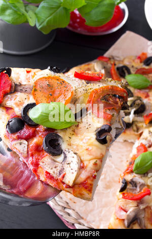 pizza with tomatoes, mushrooms, olives and peppers served on a wooden table - Stock Photo
