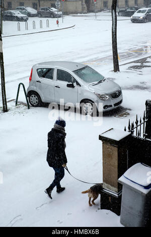 Parked car on pavement, woman walking her dog, snow in town, Strasbourg, Alsace, France. - Stock Photo