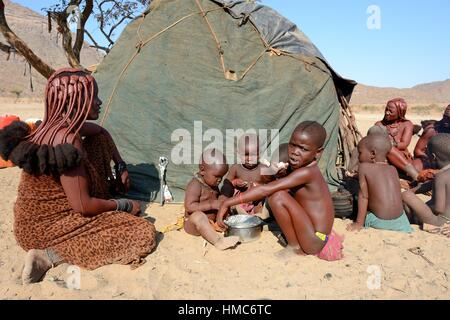 Himba children eating maize flour cooked with milk, their meal of the day, Marienfluss valley, Kaokoland desert, - Stock Photo