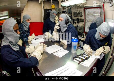 TIMOR SEA (July 7, 2015) Sailors review damage control information in a repair locker aboard the Nimitz-class aircraft - Stock Photo