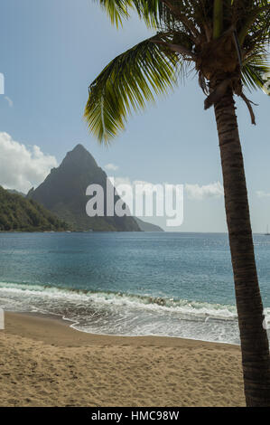 Beach view across the bay at Soufriere to the sea and Piton mountain. Framed with a palm tree - Stock Photo
