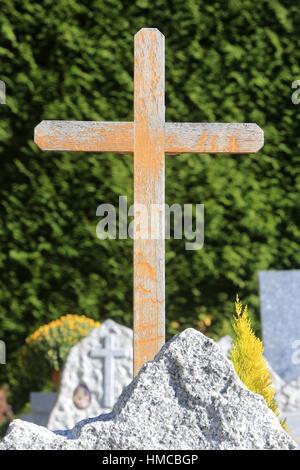 Croix en bois sur une pierre tombale. - Stock Photo