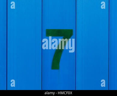 The number seven (7), in green, on a blur surface which is made out of wood - Stock Photo