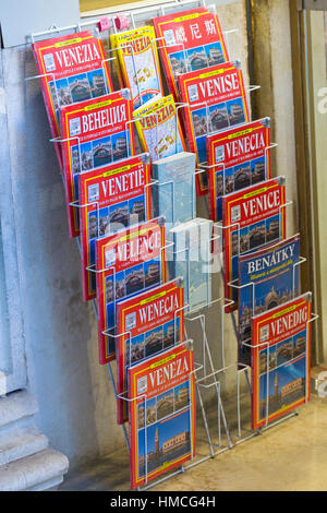 Travel Guide Books in different languages for sale on display in rack at Venice, Italy in January - Stock Photo