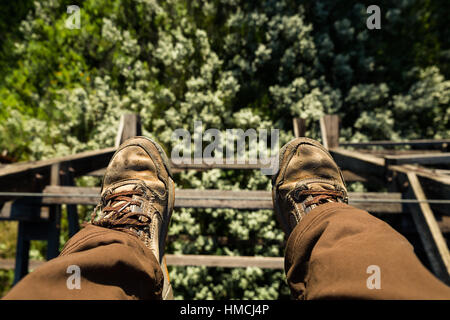 View looking down from the top of an abandoned railroad trestle roughly 80 feet off the ground above trees and brush - Stock Photo