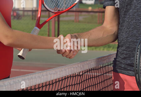 Young players shaking hands on tennis court, only hands can be seen. Healthy fitness concept with active lifestyle. - Stock Photo