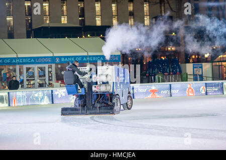 The ice on the Rink at Bryant Park in New York is prepared between ice skating sessions by a worker on a Zamboni - Stock Photo