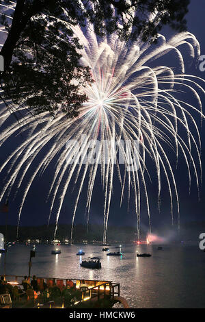People on a deck and in boats watch fireworks explode over Lake Freeman, Monticello, Indiana, USA during the annual - Stock Photo