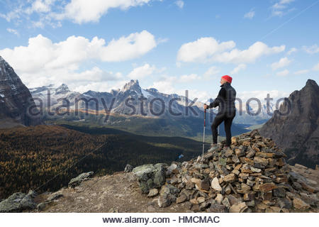 Mountain hiker on pile of rocks looking at mountain view, Lake O - Stock Photo