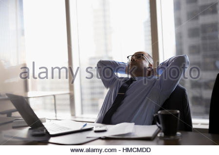 Tired male lawyer with hands behind head in conference room - Stock Photo