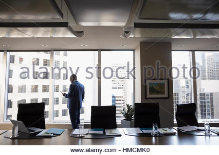 Lawyer texting with cell phone at urban conference room window - Stock Photo