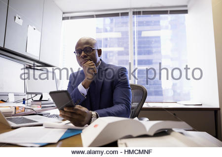 Male lawyer using cell phone in office - Stock Photo
