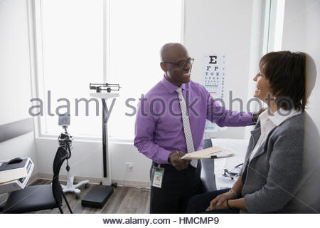 Caring male doctor talking with female patient in clinic examination room - Stock Photo
