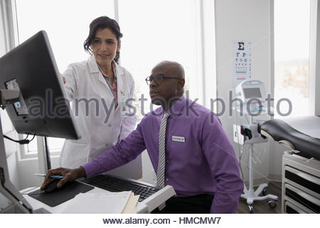Female and male doctors using computer in clinic examination room - Stock Photo