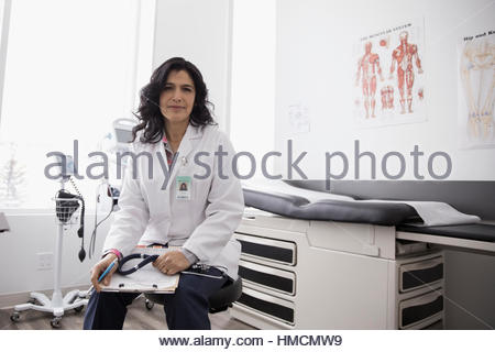 Portrait confident female doctor with clipboard in clinic examination room - Stock Photo