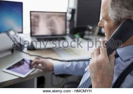 Male doctor talking on telephone and using digital tablet in clinic doctor - Stock Photo