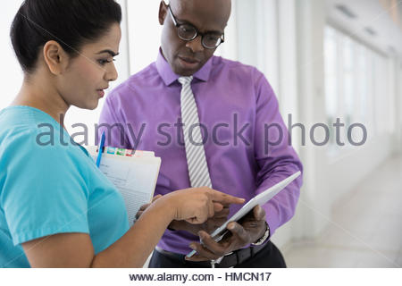 Male doctor and female nurse with medical chart consulting, using digital tablet in clinic corridor - Stock Photo