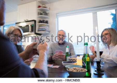 Senior couple friends playing poker and drinking beer - Stock Photo