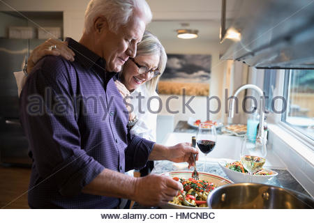 Senior couple cooking and drinking wine in kitchen - Stock Photo