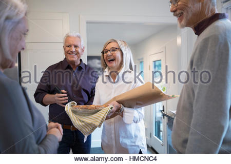 Senior couple with flowers and pie arriving at dinner party - Stock Photo