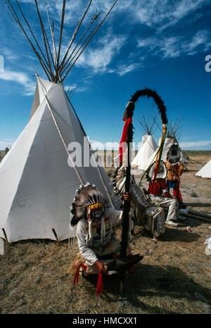 Native American wearing traditional clothes and feather headdress in front of tribal tents, annual commemoration - Stock Photo